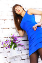 Girl in a blue dress beautiful on background of white brick wall Stock Image