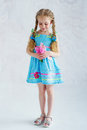 Girl in blue dress with flowers beautiful little wearing summer and holding delicate pink Stock Image