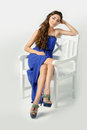 Girl in a blue dress sitting on high chair posing studio Royalty Free Stock Photos