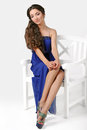 Girl in a blue dress sitting on high chair posing studio Royalty Free Stock Image