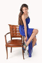 Girl in a blue dress sitting on high chair posing studio Stock Photo