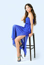 Girl in a blue dress sitting on high chair posing studio Royalty Free Stock Photography