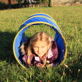Girl in blue kids tunnel little lying for Royalty Free Stock Images