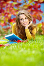 Girl with book in the autumn park Stock Photos