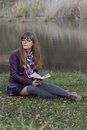 The girl with a book by the lake young reading at Royalty Free Stock Images