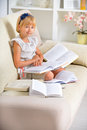 Girl with books sitting on sofa many little reader education Stock Photos