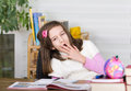 Girl is bored school yawns over books and homework Stock Photos