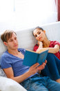 Girl boring while her boyfriend reading book Stock Photos