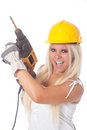 Girl with boring machine sexy young blonde working as building labor a yellow helmet and Royalty Free Stock Image