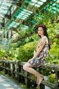 Girl in botanic garden beautiful wearing floral wreath sitting Royalty Free Stock Image