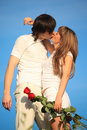 Girl with bouquet kisses guy against sky Royalty Free Stock Photos