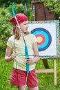 Girl with bow near sport aim in sunny summer day Stock Image