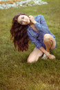 The girl bowed her head and her hair brunette in denim shirt sitting on grass Stock Photos