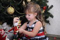 Girl with a box with a gift near the Christmas tree Stock Photos