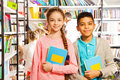 Girl and boy with books standing in library Royalty Free Stock Photo