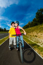 Girl and boy exercising outdoor active young people rollerblading cycling Stock Image