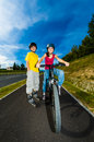 Girl and boy exercising outdoor active young people rollerblading cycling Royalty Free Stock Photo