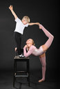 Girl and boy gymnast took graceful pose at chair Royalty Free Stock Photography