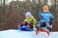 Girl and boy intend drive from hill on sledges Stock Images