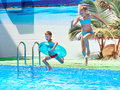 Girl and boy jumping into resort pool Royalty Free Stock Photo