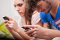 Girl and boy looking at their mobile phones Royalty Free Stock Photo