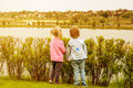 A girl and a boy looking to another bank of the river at a sunset. Royalty Free Stock Photo