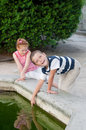 Girl and boy playing by the fountain in a park Stock Photography