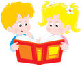 Girl and boy read a book Stock Photos