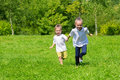Girl and boy running on the grass Royalty Free Stock Photo