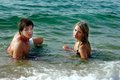 Girl and boy in a sea on sandy beach the water Royalty Free Stock Photos