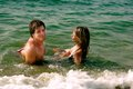 Girl and boy in a sea on sandy beach the water Royalty Free Stock Photography