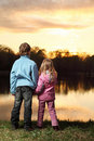 Girl and boy standing back on bank of river Royalty Free Stock Photo