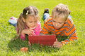 A girl and a boy with tablet computer are looking at the screen of while lying on green lawn Royalty Free Stock Image