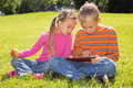 A girl and a boy with tablet computer are looking at the screen of while lying on green lawn Royalty Free Stock Images