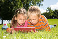 A girl and a boy with tablet computer are looking at the screen of while lying on green lawn Stock Images