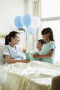 Girl and boy visiting their mother in the hospital giving present and balloons Stock Photography