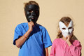Girl and boy wear masks and look at camera Royalty Free Stock Image