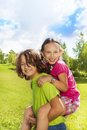 Girl on boys back boy carry his both happy and smiling in the park sunny summer day Royalty Free Stock Photo