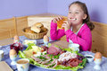 Girl at breakfast little while richly laden Stock Photo