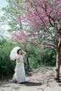 stock image of  Girl bride under a flowering tree with pink flowers