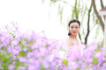 Girl bride in wedding dress with elegant hairstyle in Orychophragmus violaceus flower field Royalty Free Stock Photo