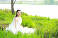Girl bride in wedding dress with elegant hairstyle, with white wedding dress Sitting in the grass by the river Royalty Free Stock Photo