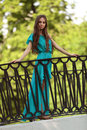 Girl on the bridge beautiful in a blue summer dress is standing Stock Photos