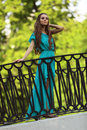 Girl on the bridge beautiful in a blue summer dress is standing and looking afar Stock Images