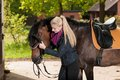 Girl bridles her horse brown new forest pony Stock Photography