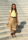 Girl in brown and yellow skirt smiling tropical young woman t shirt standing front of grey stairs Stock Images