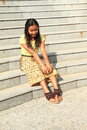 Girl in brown and yellow skirt surprised tropical young woman t shirt sitting on grey stairs Royalty Free Stock Photography