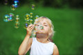 Girl with bubble blower little play on green lawn Stock Images