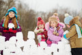 Girl build wall from snow bricks with three children little Stock Photo