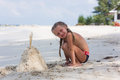 Girl is building on the beach sandcastles in the summer sunny day Royalty Free Stock Photo